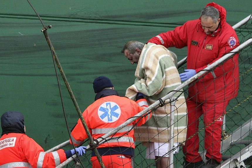 """A wounded passenger is helped as he leaves from the """"Spirit of Piraeus """" cargo container ship after the car ferry Norman Atlantic caught fire in waters off Greece on Dec 29, 2014. -- PHOTO: REUTERS"""