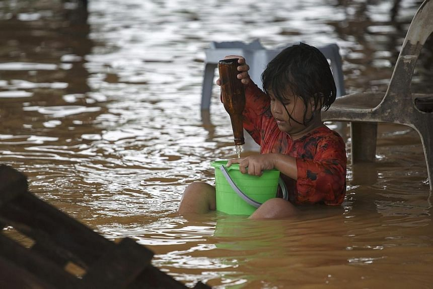 A girl plays on a flooded street on the outskirts of Kota Bharu in Kelantan on Dec 29, 2014.Flood relief efforts in Malaysia will be given a boost of $100,000 from the Singapore Government, revealed a statement from Singapore's Ministry of Fore