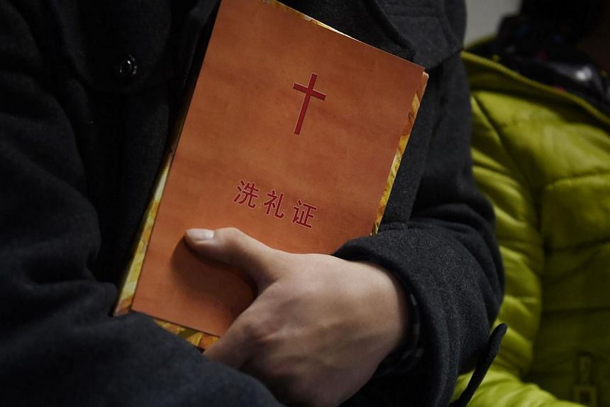 A man holds a certificate of baptism after he was baptised during a Christmas Eve service held by members of an underground church, at an apartment in Beijing, on Dec 24, 2014. China's Christian groups have long been subject to crackdowns, but the at