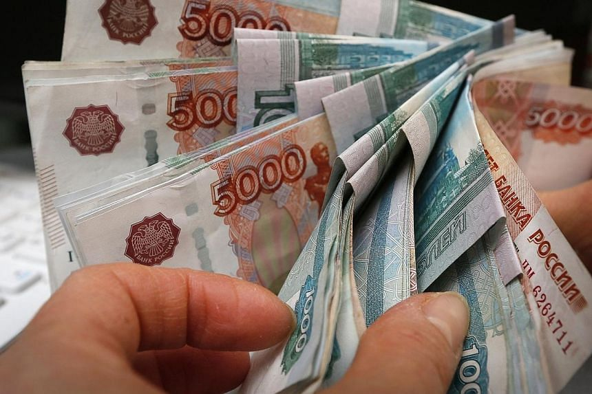 An employee counts Russian rouble banknotes at a small private shop selling home appliances in Krasnoyarsk on Dec 26, 2014. -- PHOTO: REUTERS