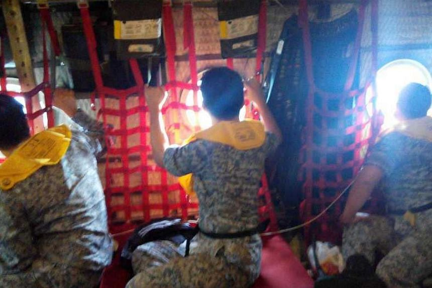Singapore Air Force personnel on board the C-130 plane assisting with the search-and-locate efforts of missing AirAsia flight QZ8501. -- ST PHOTO: FENG ZENGKUN