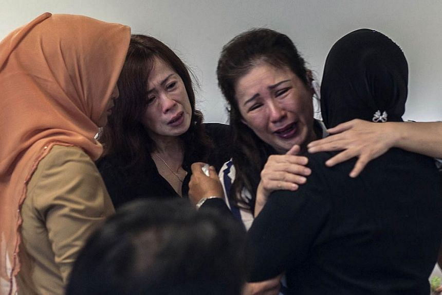 Family members of passengers from AirAsia flight QZ8501 gather at the airport in Surabaya, East Java, on December 29, 2014. The plane which went missing with 162 people on board en route to Singapore is likely at the bottom of the sea, Indonesia's Na