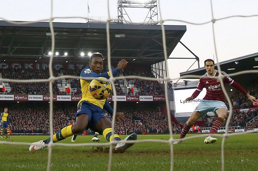 Arsenal's Danny Welbeck (second, right) shoots to score a goal against West Ham United during their English Premier League soccer match at Upton Park in London. -- PHOTO: REUTERS