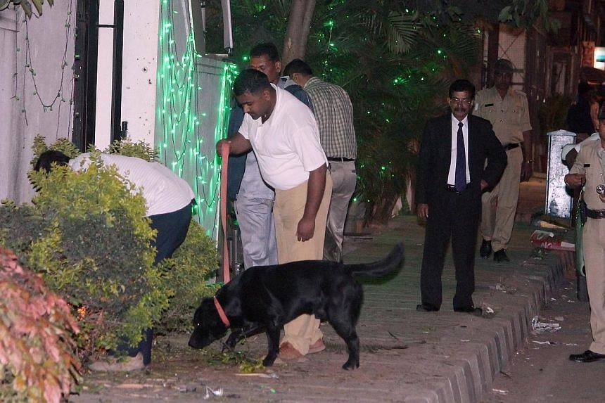 Bomb squad personnel along with sniffer dogs scour the blast site for evidence following a low intensity blast from an Improvised Explosive Device (IED). -- PHOTO: AFP
