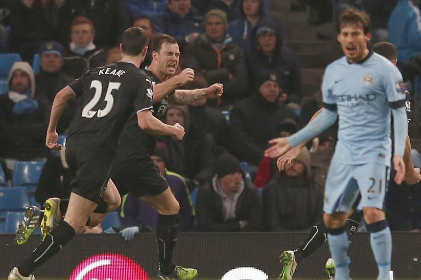Burnley's Ashley Barnes (second, left) celebrates with team-mates after scoring a goal against Manchester City during their English Premier League soccer match at the Etihad Stadium in Manchester, northern England on Dec 28, 2014. -- PHOTO: REUTERS