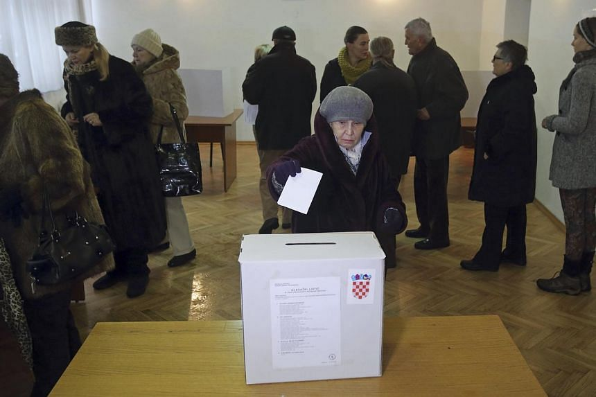 A woman casts her ballot at a polling station during the presidential election in Zagreb on Dec 28, 2014. -- PHOTO: REUTERS