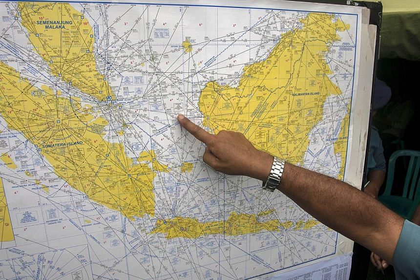 An Indonesian Air Force official shows a map to journalists of the search area for the missing AirAsia Indonesia flight QZ8501, at the airport in Surabaya, East Java, on Dec 29, 2014. -- PHOTO: AFP