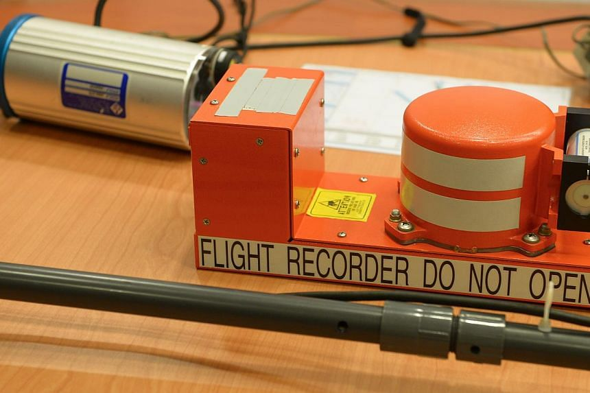 A close-up of a flight recorder with parts from the Underwater Locator Beacon Detector System in the background. -- ST PHOTO: NG SOR LUAN
