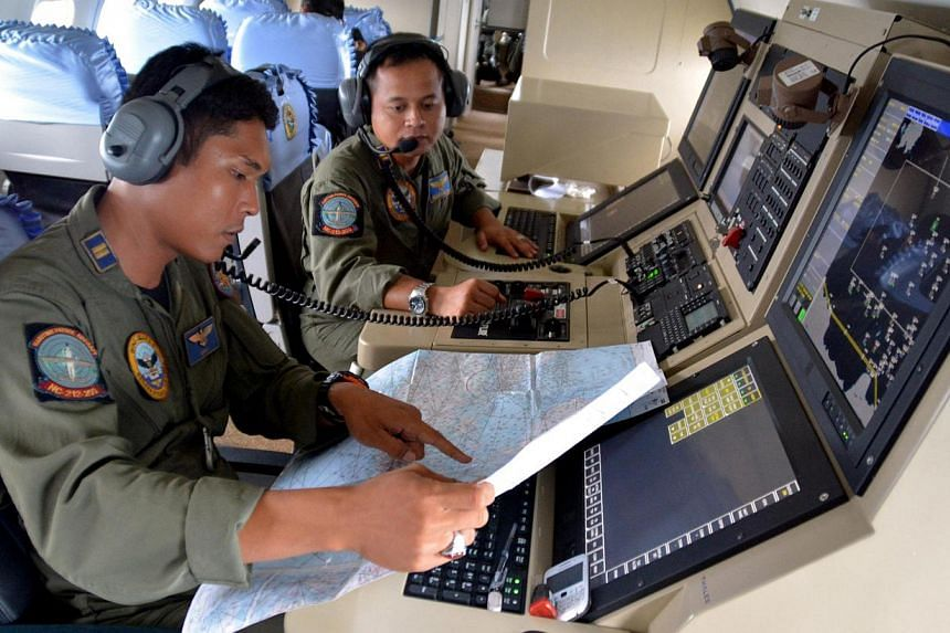 Two members from the Indonesian Navy's Tactical Commanding Operator (TACCO) help with the search for AirAsia flight QZ8501on board a CN235 aircraft over Karimun Java in the Java Sea on Dec 28, 2014. The head of Indonesia's Meteorology, Climatology an