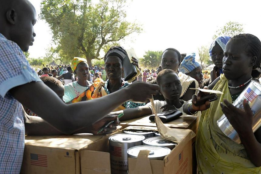 Internally displaced South Sudanese receive cooking oil and food aid from the World Food Programme in Bor, Jonglei state, on Dec 10, 2014. The United Nations saidit had begun delivering food aid to war-torn South Sudan via the Nile River from S