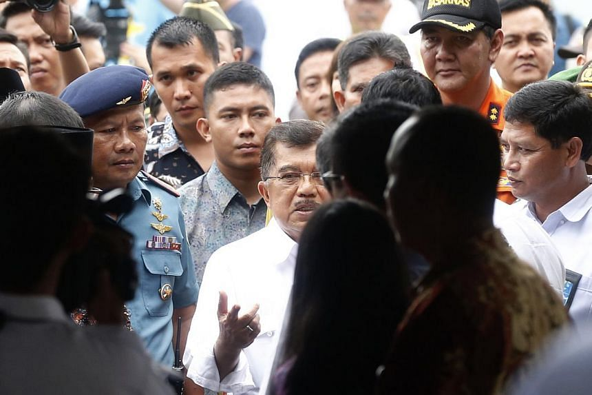 Indonesian Vice-President Jusuf Kalla (centre) speaking to AirAsia CEO Tony Fernandez (blocked) upon his arrival at the crisis centre at Juanda International Airport Terminal 2 on Dec 29, 2014. -- ST PHOTO: KEVIN LIM