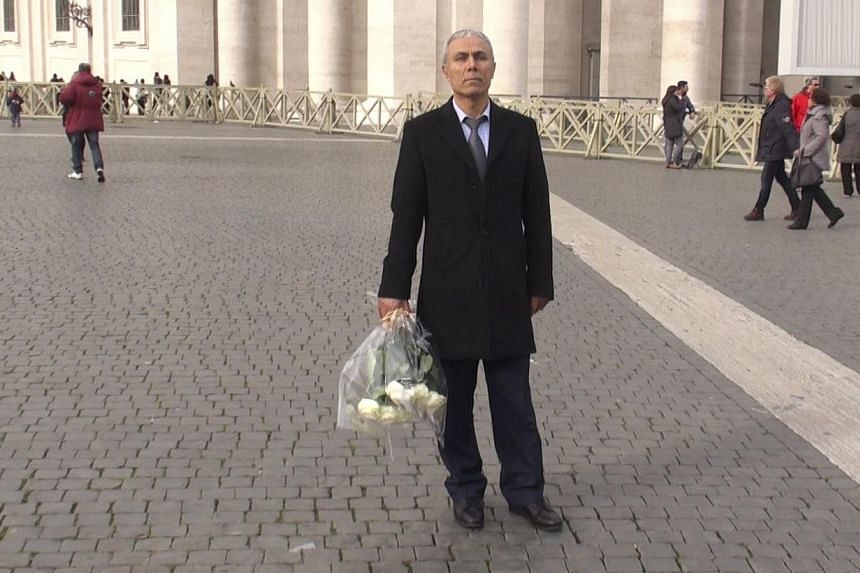 A handout photo grabbed from a video made and released by ADNKronos on Dec 27, 2014, shows Mehmet Ali Agca, the Turkish former extremist who attempted to assassinate Pope John Paul II in 1981, holding a wreath of flowers on St Peter's square in The V