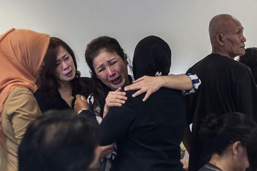 Family members of passengers from missing Malaysian air carrier AirAsia flight QZ8501 gather at the airport in Surabaya, East Java, on Dec 29, 2014. -- PHOTO: AFP
