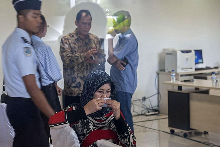 A relative of a passenger from missing Malaysian air carrier AirAsia flight QZ8501 gather at the airport in Surabaya, East Java, on Dec 29, 2014. -- PHOTO: AFP