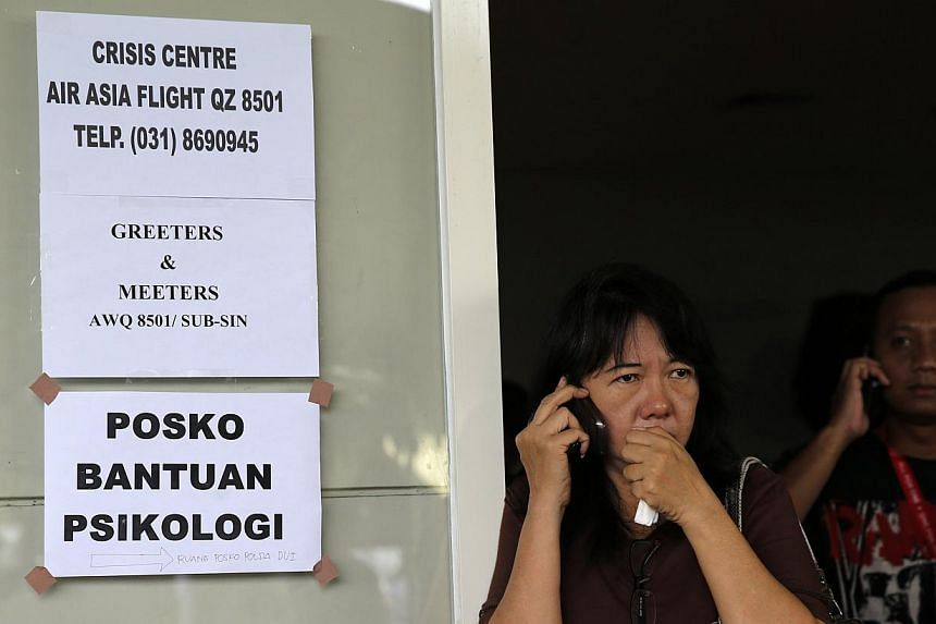 A family member of passengers onboard the missing AirAsia flight QZ8501 speaks on her mobile phone as she awaits news of the airplane at a waiting area in Juanda International Airport, Surabaya on Dec 29, 2014. -- PHOTO: REUTERS