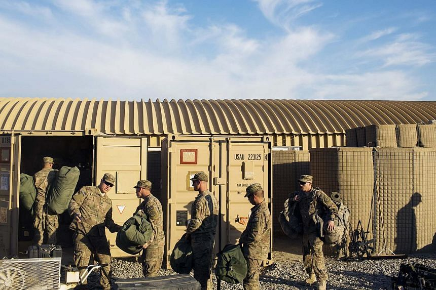 US soldiers from D Troop of the 3rd Cavalry Regiment load bags into a container in preparation for leaving Afghanistan at forward operating base Gamberi in the Laghman province on Dec 28, 2014. -- PHOTO: REUTERS
