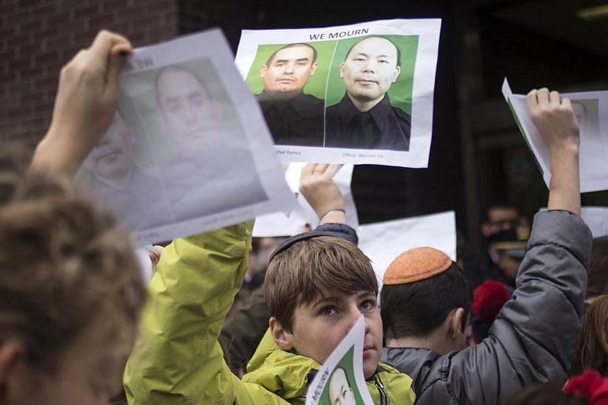 A school boy at an event to show support for police officers in New York on Dec 22, 2014, holds images of slain New York Police Department officers Wenjian Liu (right) and Rafael Ramos, who were shot and killed as they sat in a marked squad car on De