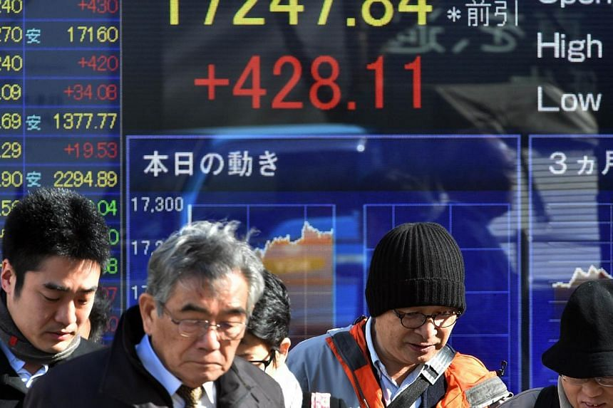 Pedestrians pass before a share prices board in Tokyo on Dec 18, 2014. -- PHOTO: AFP