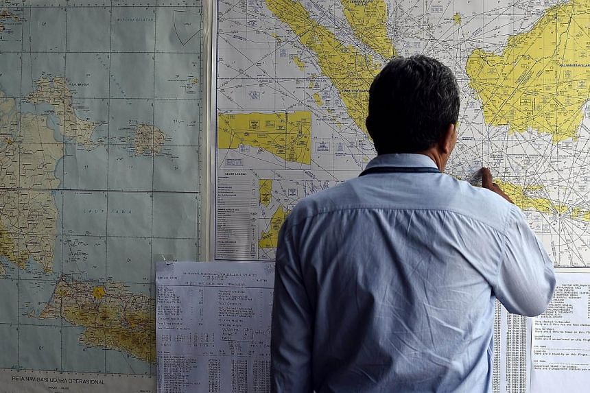 A man looks at a map showing the search area for the missing AirAsia flight QZ8501 outside the crisis centre set up at Juanda International Airport in Surabaya on Dec 29, 2014. -- PHOTO: AFP