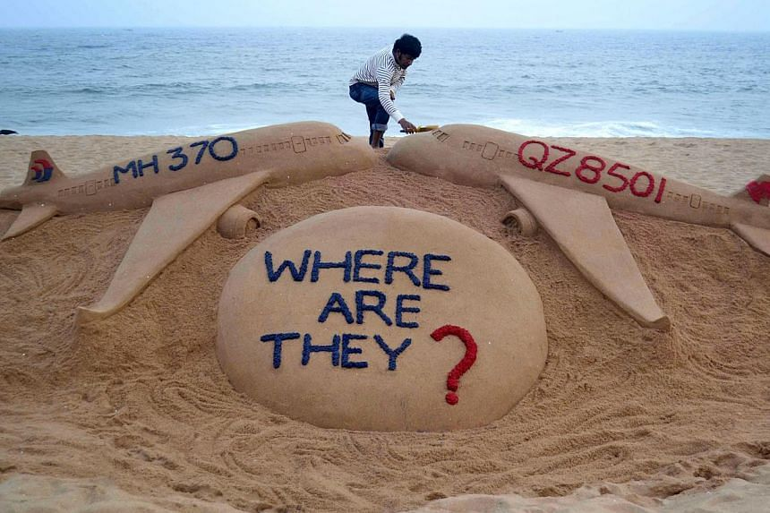 Indian sand artist Sudarsan Pattnaik giving the final touches to his sand sculpture portraying two missing aircraft, AirAsia QZ8501 and Malaysia Airlines MH370, on Golden Sea Beach at Puri, some 65km east of Bhubaneswar, on Dec 29, 2014. -- PHOTO: AF