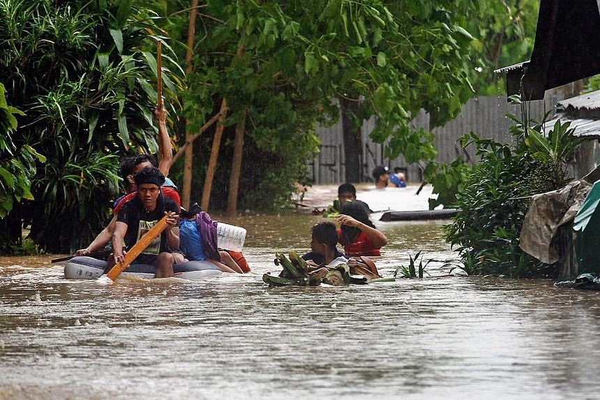 Residents help each other out from their inundated neighbourhoods after rains spawned by a tropical storm, locally known as Seniang, caused flooding in Misamis Oriental on the southern Philippine island of Mindanao on Dec 29, 2014. -- PHOTO: AFP