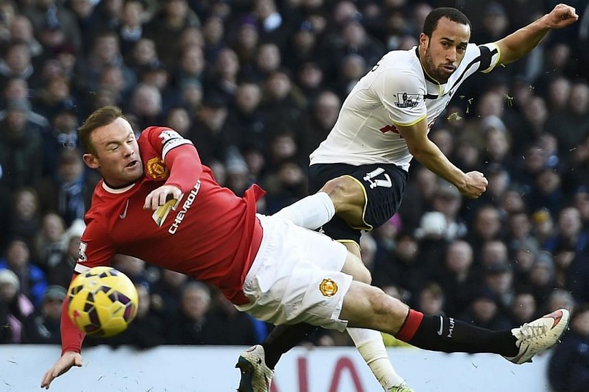 Manchester United's Wayne Rooney (left) challenges Tottenham Hotspur's Andros Townsend during their English Premier League soccer match at White Hart Lane in London Dec 28, 2014. -- PHOTO: REUTERS
