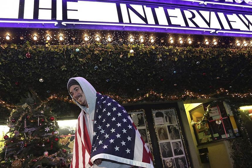 """A man waiting outside a theatre in Los Angeles on Christmas Eve for a midnight screening of The Interview. It is ironic that the film's release was seen as a victory for free speech in a country where it is politically incorrect to wish people """"M"""