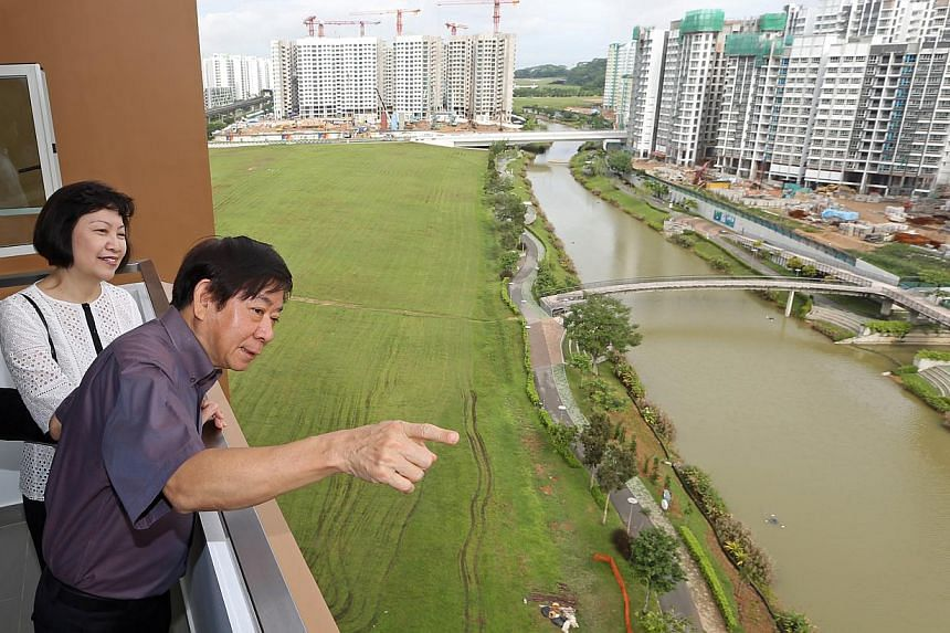 Mr Khaw Boon Wan and HDB chief executive Cheong Koon Hean viewing the projects along Punggol Waterway from a newly completed five-room flat yesterday, when Mr Khaw attended the handover of a block in the Waterway Woodcress project. -- ST PHOTO: SEAH
