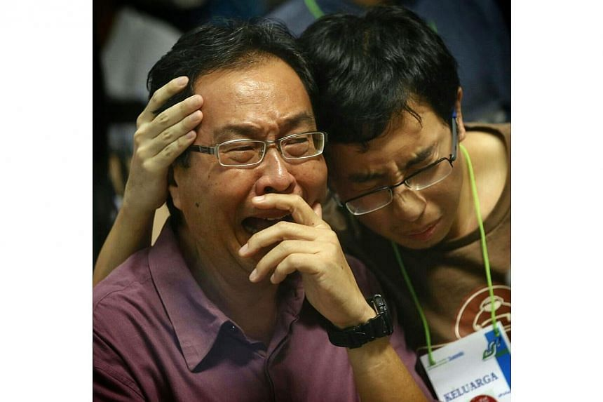 F.Y. Widodo (left) and Andy Paul Chen, the father and boyfriend respectively of missing passenger Florentina Maria Widodo, react in the crisis centre at Juanda International Airport Terminal 2 in Surabaya after watching first footages of a dead body