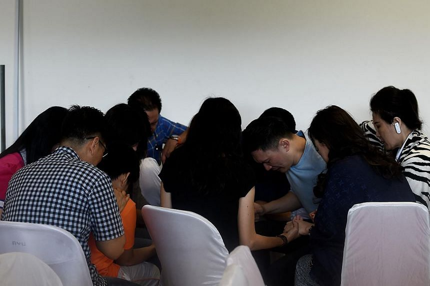 Family members of passengers onboard missing Malaysian air carrier AirAsia flight QZ8501 pray together while waiting for a briefing inside the crisis-centre set up at Juanda International Airport in Surabaya on Dec 30, 2014.