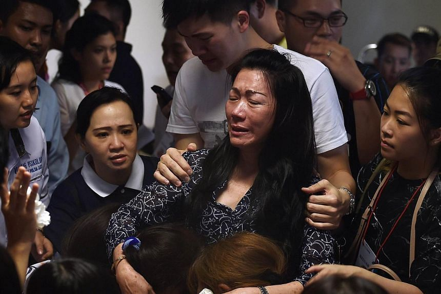 Family members of passengers onboard the missing Malaysian air carrier AirAsia flight QZ8501 react after watching news reports showing an unidentified body floating in the Java sea, inside the crisis-centre set up at Juanda International Airport in S