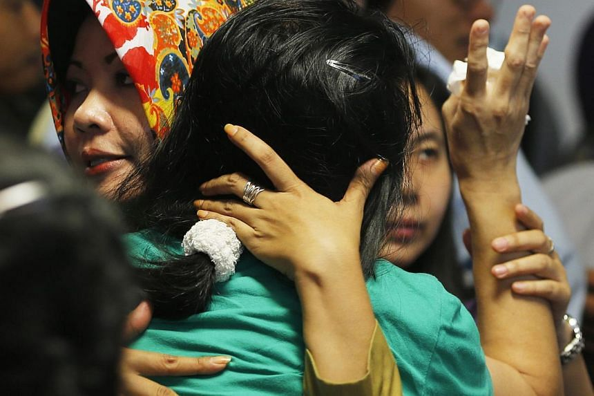 A government official (left) tries to calm a family member of passengers onboard AirAsia flight QZ8501 at a waiting area in Juanda International Airport, Surabaya on Dec 30, 2014. -- PHOTO: REUTERS
