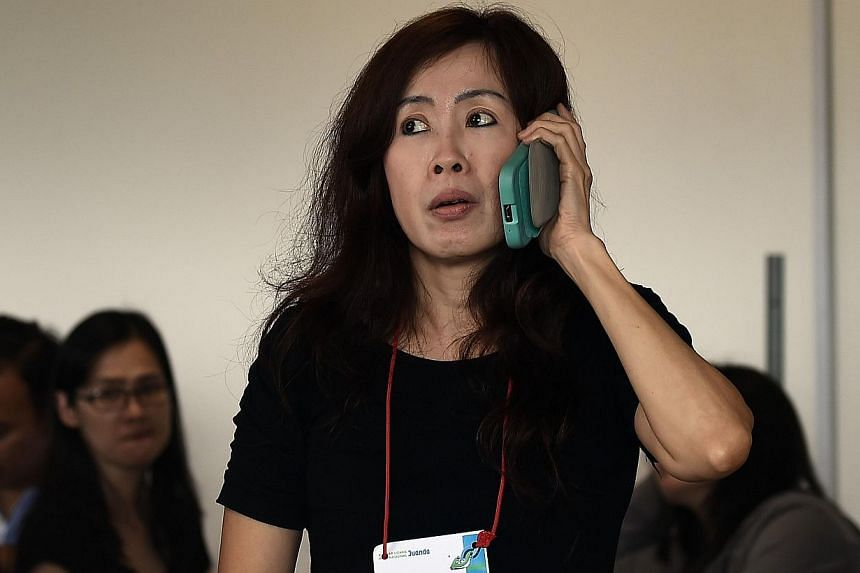 Family members of passengers onboard the missing Malaysian air carrier AirAsia flight QZ850, react to news of floating debris spotted in the search area, inside the crisis-centre set up at Juanda International Airport in Surabaya on Dec 30, 2014. --