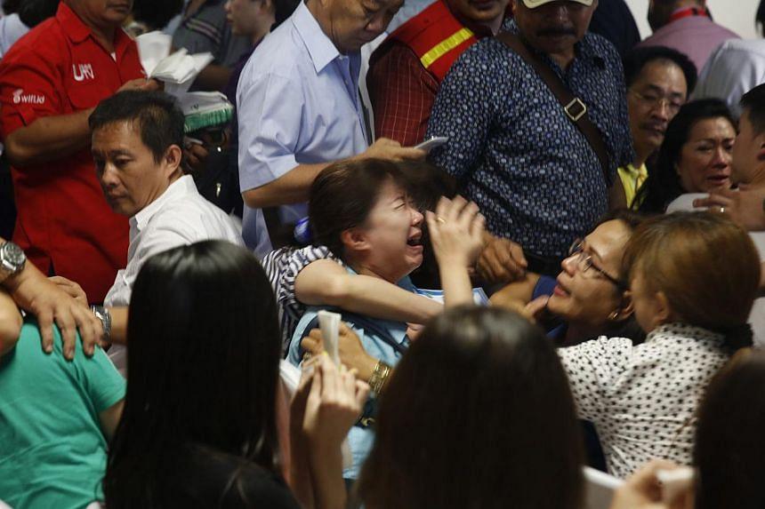 Distraught family members of passengers onboard AirAsia flight QZ8501 react at a waiting area in Juanda International Airport, Surabaya on Dec 30, 2014. -- PHOTO: REUTERS