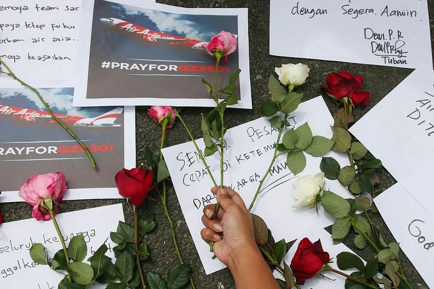Indonesian people pray for passengers of the missing AirAsia flight QZ8501 in Malang, East Java on Dec 30, 2014. -- PHOTO: AFP