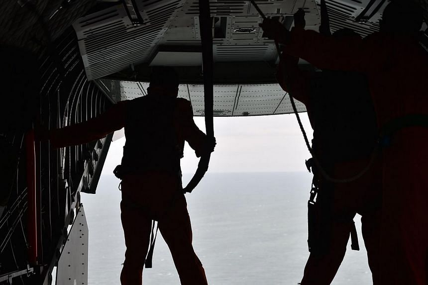 Indonesian air force CN295 crew members take part in a search and locate operation for the missing plane near Pangkalan, Central Kalimantan on Dec 30, 2014. -- PHOTO: AFP