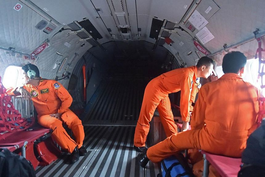 Indonesian air force CN295 crew members during a search and locate operation for the missing plane near Pangkalan, Central Kalimantan on Dec 30, 2014. -- PHOTO: AFP