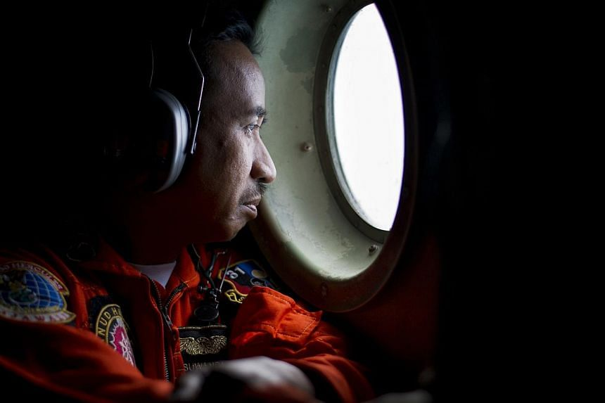 A member of an Indonesian Hercules C130 aircrew watching through a window while monitoring the Belitung Timur sea during search operations for AirAsia flight QZ8501 near Belitung island, on Dec 29, 2014. -- PHOTO: REUTERS
