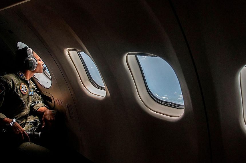 A member of the Indonesian military looking out of the window during a search and rescue operation for missing Malaysian air carrier AirAsia flight QZ8501, over the waters of the Java Sea on Dec 29, 2014. -- PHOTO: AFP