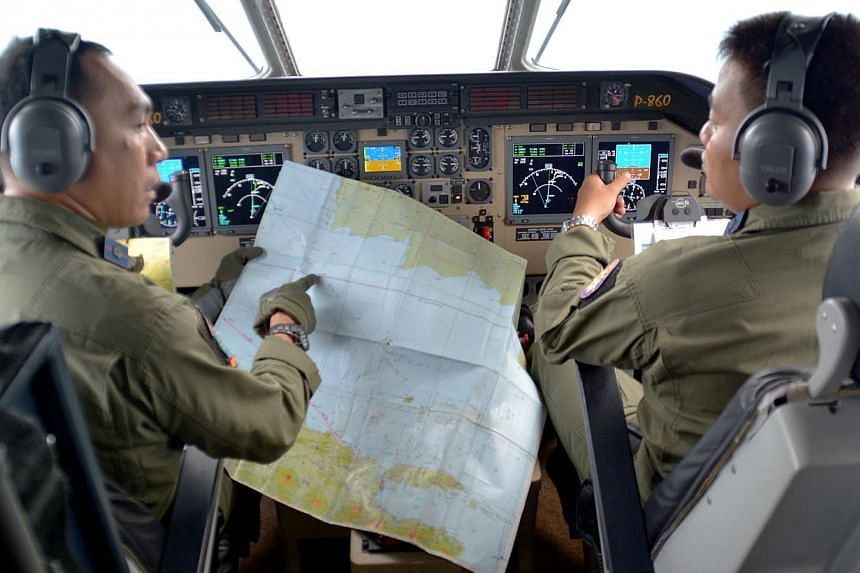 Pilot of Navy airplane CN235 M. Naim holding a map to co-pilot Rahmad while flying over the Java sea during joint search operations of AirAsia flight QZ8501 on Dec 29, 2014. -- PHOTO: REUTERS