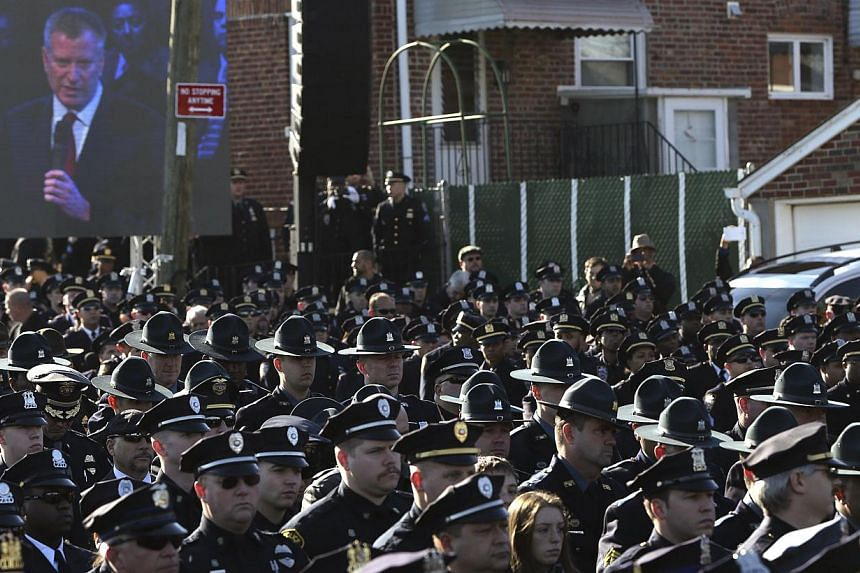 Law enforcement officers turn their backs on a video monitor as New York City Mayor Bill de Blasio speaks during the funeral of slain New York Police Department officer Rafael Ramos on Dec 27, 2014. De Blasio drew heckles and boos as well as cheers o