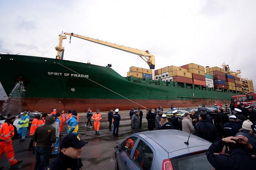 The Singapore-flagged cargo container ship Spirit of Piraeus, carrying 49 passengers evacuated from the ferry Norman Atlantic, arriving in the harbour of Bari on Dec 29, 2014, as Italian advanced rescue personnel and police wait on the quay. -- PHOTO