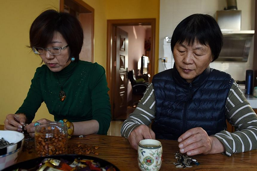 Relatives of passengers from the missing Malaysia Airlines flight MH370, Xu Jinghong (left) and Dai Shuqin sit at a table at Xu's home in Beijing on Dec 30, 2014. -- PHOTO: AFP