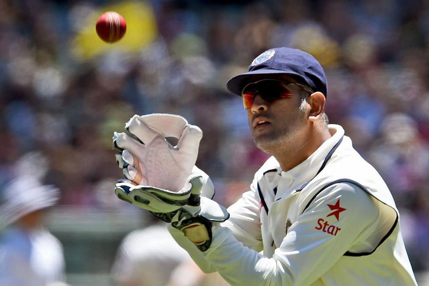 Indian wicketkeeper Mahendra Singh Dhoni catches the ball from the outfield during the second day of the third cricket Test match against Australia at the Melbourne Cricket Ground (MCG) in Melbourne on Dec 27, 2014. Dhoni announced his retiremen