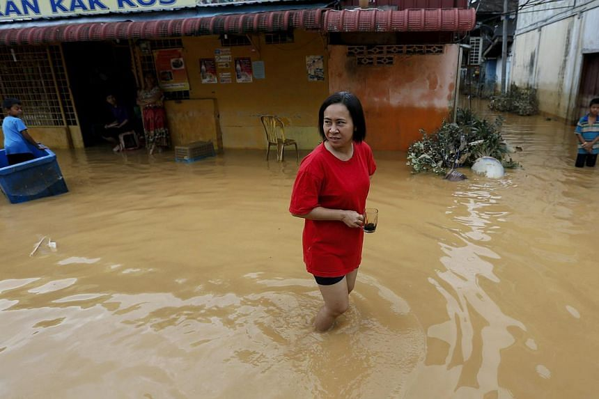 A woman holds her coffee cup as she walks through a flooded street on the outskirt of Kota Bharu in Kelantan on Monday, Dec 29, 2014.Malaysia's worst flooding in a decade has forced nearly a quarter of a million people from their homes, officia