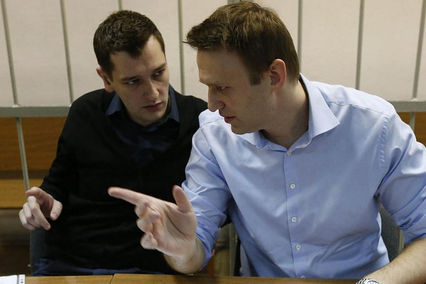 Russian opposition leader and anti-corruption blogger Alexei Navalny (right) talks to his brother and co-defendant Oleg before a court hearing in Moscow on Dec 19, 2014. A Russian court ruled on Tuesday, Dec 30, 2014, to give Alexei Navalny a su