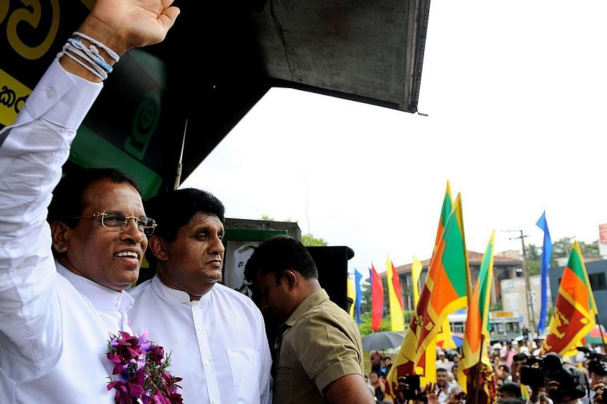 Sri Lanka's main opposition presidential candidate Maithripala Sirisena (left) waves to supporters ouside the Election Commission office on Dec 8, 2014. Sri Lanka's largest Tamil party, the Tamil National Alliance, on Dec30, 2014, endorsed Mr Sirisen