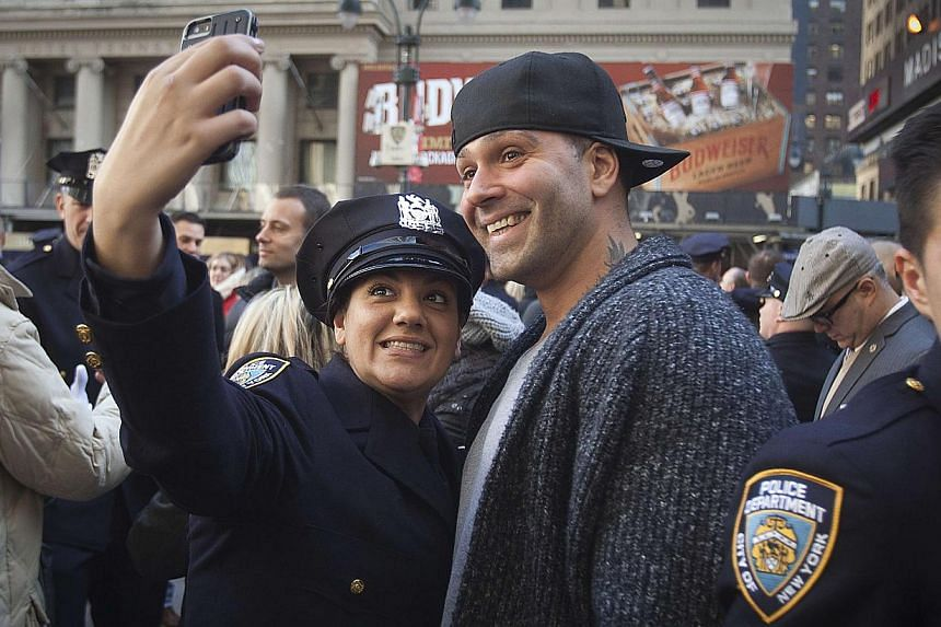 A new New York City Police officer takes a photo after her graduating class ceremony in New York Dec 29, 2014. Hundreds of officers took part in the ceremony at Madison Square Gardens. -- PHOTO: REUTERS