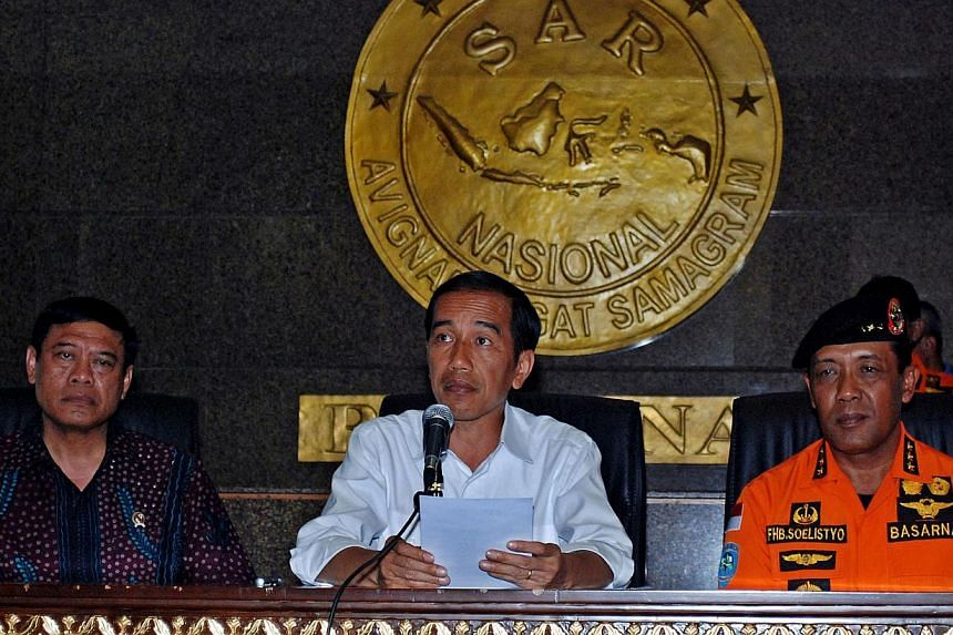 Indonesia's President Joko Widodo (centre) said recovering the remains of victims and debris will remain the topmost priority of the search and rescue operations team out at sea near the crash site of AirAsia flight QZ8501.-- PHOTO: AFP