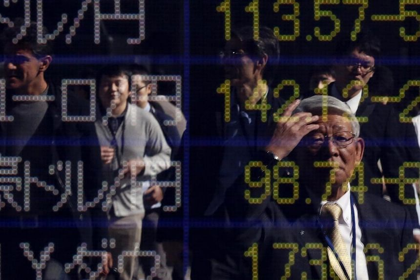 A pedestrian is reflected in an electronic board showing exchange rates between the Japanese yen and the US dollar, the euro, and other currencies outside a brokerage in Tokyo on Nov 4, 2014. -- PHOTO: REUTERS